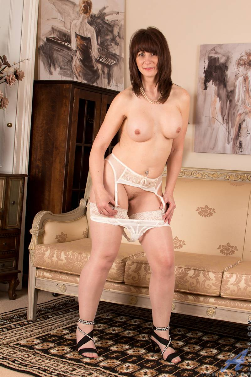 Mature housewife Toni Lace playing with her pussy on the sofa at Anilos